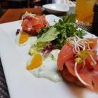 Foto zu Q1 Metropolitan Kitchen & Bar: Hausgebeizter Campari-Lachs mit Kartoffelrösti, Basilikumcrème, Granatapfelkerne, Orangenfilets