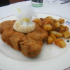 Paniertes Kotelett mit Bratkartoffeln und Gurkensalat