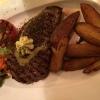 Amerikanisches Rindersteak vom Grill (300 gr.) mit Kräuterbutter, Pfeffertomate und Country Potados ( 14,90 €)