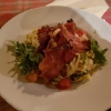 Tagliatelle mit Rucola, Kirschtomaten in Ziegenkäserahm, Knusperschinken und Parmesan für 11,80 €