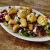 Couscous-Bällchen auf bunten Salat mit Granatapfelkernen, Joghurt-Minz-Soße und auf meinen Wunsch Kartoffeln statt Brot.