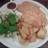 Schweinefleischschnitzel po Odessky serviert mit Salatgarnitur dazu hausgemachte Bratkartoffeln
