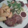 Rindmedaillons mit scharfer Tomatensauce (mariniertes Rinderfilet, serviert auf pikantem Spinat) mit Bratkartoffeln
