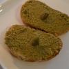 Gruß aus der Küche mit zwei Scheiben Baguette Brot mit Olivenpaste und einer Kaper