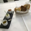 Hausgemachte Brote (rechts: Baguette, Mitte: Walnussbrot, links: Focaccia) mit einem Tomaten-Dip, Butter mit Limette und Thymian, sowie Olivenöl.