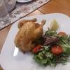 Kleiner Gockel frisch aus dem Ofen mit Zitrone, Blattsalaten und Brot