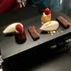 Petit Fours: Canelé mit Passionsfruchtschaum und Himbeere; ein Vanille-Eis auf Streuseln und kleine Brownies.