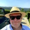 Dicker Mann mit Hut grinst debil im Hochformat