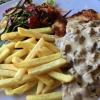 Pilz-Sahne-Schnitzel, ein Bio-Schnitzel vom Landschwein mit Pommes und frischen Pilzen der Saison in einer cremigen Weißwein-Sahne-Sauce, dazu ein kleiner Wildkräutersalat