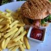 Advokaten-Burger, ein Rinderhacksteak mit Gurke, saftigen Tomaten, Wildkräutern, Zwiebeln, kross gebratenem Bacon, hausgemachter Sauce und Pommes