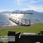 Foto zu Cafe-Restaurant Inselblick: Chiemseestrand mit Blick zur Fraueninsel vom Cafe-Restaurant Inselblick