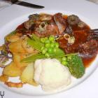 Foto zu Augustenstüble: Geschmorte Kalbshaxe in Scherrysauce mit frischen Morcheln und Bratkartoffeln